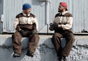 Two workers sit chatting.