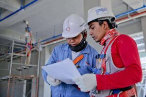 Two men wearing hard hats look at plans
