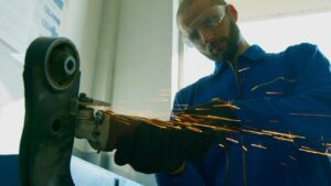 A man uses a welder in the manufacturing process