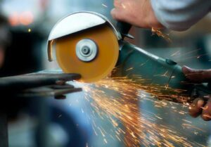 A man uses an angle grinder to cut into metal.
