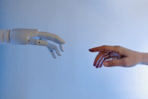 A robotic hand reaches out to a human hand