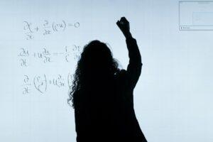 A person writes formulas on a board