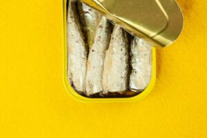 An open can of sardines on a yellow background