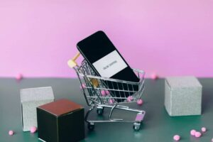 A mini shopping cart with a cellphone in it