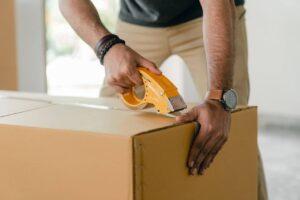 A man seals a box of goods